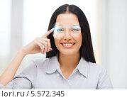 Купить «улыбающаяся девушка показывает на свои футуристические очки», фото № 5572345, снято 6 ноября 2013 г. (c) Syda Productions / Фотобанк Лори