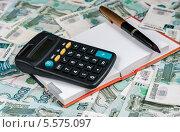 Купить «Ручка, блокнот и калькулятор лежат на фоне из российских денег», эксклюзивное фото № 5575097, снято 10 февраля 2014 г. (c) Игорь Низов / Фотобанк Лори