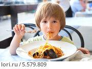 Купить «Ребенок ест макароны с мидиями», фото № 5579809, снято 10 июля 2012 г. (c) Юлия Кузнецова / Фотобанк Лори