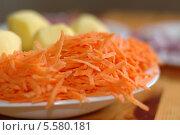 Морковь, натертая на терке, и очищенный картофель на столе. Стоковое фото, фотограф Insomnia / Фотобанк Лори