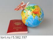 Купить «Российский загранпаспорт, глобус и самолетик, сложенный из пятитысячной купюры, на сером фоне», фото № 5582197, снято 9 февраля 2014 г. (c) Алексей Карпов / Фотобанк Лори