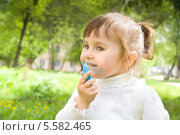 Купить «Симпатичная девочка балуется синим мелом на открытом воздухе», фото № 5582465, снято 11 мая 2013 г. (c) Александр Волков / Фотобанк Лори