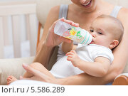 Купить «Mother feeding baby with milk bottle», фото № 5586289, снято 17 ноября 2013 г. (c) Wavebreak Media / Фотобанк Лори