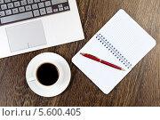 Купить «Рабочее место: клавиатура ноутбука, чашка с кофе на блюдце и блокнот с ручкой на деревянном столе, вид сверху», фото № 5600405, снято 21 марта 2013 г. (c) Sergey Nivens / Фотобанк Лори