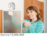 Купить «Счастливая женщина протирает стекло от пыли», фото № 5600969, снято 17 октября 2018 г. (c) Яков Филимонов / Фотобанк Лори