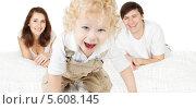 Купить «Счастливая семья, радостный ребёнок на переднем плане и родители», фото № 5608145, снято 18 ноября 2012 г. (c) Инара Прусакова / Фотобанк Лори