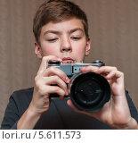 Юный парень держит в руках старый плёночный фотоаппарат. Стоковое фото, фотограф Игорь Низов / Фотобанк Лори