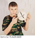 Купить «Подросток держит в руках настенные часы», фото № 5629669, снято 6 апреля 2013 г. (c) Наталья / Фотобанк Лори