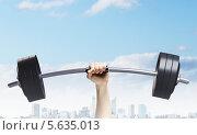 Купить «Сильная рука поднимает вверх штангу на фоне современного города», фото № 5635013, снято 19 марта 2019 г. (c) Sergey Nivens / Фотобанк Лори