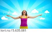 Купить «Девушка в больших наушниках поет, раскинув руки в стороны», фото № 5635081, снято 26 апреля 2013 г. (c) Sergey Nivens / Фотобанк Лори