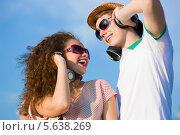Купить «Кудрявая девушка и парень в наушниках слушают музыку», фото № 5638269, снято 23 июня 2013 г. (c) Sergey Nivens / Фотобанк Лори