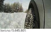 Купить «Автомобиль разворачивается на заснеженной дороге, крупный план колеса сбоку», видеоролик № 5645801, снято 26 февраля 2014 г. (c) Кекяляйнен Андрей / Фотобанк Лори