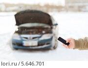 Купить «Мужская рука набирает номер аварийной службы на фоне сломанной машины с поднятым капотом», фото № 5646701, снято 16 января 2014 г. (c) Syda Productions / Фотобанк Лори