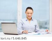 Красивая деловая женщина рассматривает графики в офисе и улыбается. Стоковое фото, фотограф Syda Productions / Фотобанк Лори