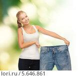 Купить «Стройная похудевшая девушка улыбается, демонстрируя джинсы большого размера», фото № 5646861, снято 23 марта 2013 г. (c) Syda Productions / Фотобанк Лори