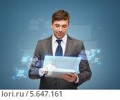 Молодой бизнесмен работает с современным приложением на планшетном компьютере. Стоковое фото, фотограф Syda Productions / Фотобанк Лори