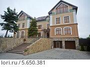 Частный двухэтажный дом с гаражом и двумя елями. Стоковое фото, фотограф Losevsky Pavel / Фотобанк Лори