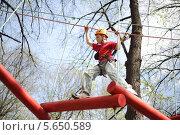 Купить «Молодой скалолаз искусно проходит по подвесному мосту на веревочном аттракционе», фото № 5650589, снято 29 апреля 2012 г. (c) Losevsky Pavel / Фотобанк Лори
