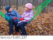 Купить «Двое детей сидят в гамаке в осеннем лесу», фото № 5651237, снято 4 ноября 2011 г. (c) Losevsky Pavel / Фотобанк Лори