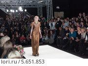 Купить «Девушка модель во время показа мод проходит по подиуму на фоне зрителей и фотографов», фото № 5651853, снято 21 марта 2012 г. (c) Losevsky Pavel / Фотобанк Лори