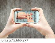 Смартфон с изображением на экране рук, показывающих решетку. Стоковое фото, фотограф Александр Басов / Фотобанк Лори