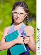Девочка в очках стоит с книгой и лупой в руках. Стоковое фото, фотограф Papoyan Irina / Фотобанк Лори