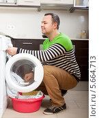 Купить «Мужчина загружает белье в стиральную машину», фото № 5664713, снято 5 июня 2020 г. (c) Дарья Филимонова / Фотобанк Лори