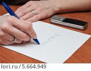 Купить «Девушка пишет заявление на листке бумаги за столом», эксклюзивное фото № 5664949, снято 3 марта 2014 г. (c) Игорь Низов / Фотобанк Лори