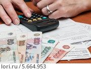 Купить «Женщина рассчитывает на калькуляторе расходы на коммунальные услуги», эксклюзивное фото № 5664953, снято 3 марта 2014 г. (c) Игорь Низов / Фотобанк Лори