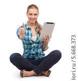 Купить «Симпатичная девушка в клетчатой блузке с планшетным компьютером в руках», фото № 5668373, снято 12 февраля 2014 г. (c) Syda Productions / Фотобанк Лори