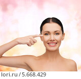 Купить «Красивая девушка показывает пальцем на кожу вокруг глаз», фото № 5668429, снято 1 декабря 2013 г. (c) Syda Productions / Фотобанк Лори