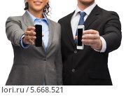 Купить «Бизнесмен и деловая девушка держат мобильные телефоны в руках», фото № 5668521, снято 12 декабря 2013 г. (c) Syda Productions / Фотобанк Лори