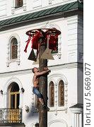 Масленица. Молодой мужчина забирается на столб за подарками (2014 год). Редакционное фото, фотограф Алексей Воронцов / Фотобанк Лори