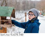 Купить «Мальчик-подросток стоит возле кормушки для птиц на улице зимой», эксклюзивное фото № 5679749, снято 5 марта 2014 г. (c) Игорь Низов / Фотобанк Лори
