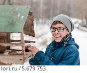 Купить «Весёлый мальчик-подросток кормит птиц зимой», эксклюзивное фото № 5679753, снято 5 марта 2014 г. (c) Игорь Низов / Фотобанк Лори