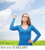 Счастливая девушка думает о чем-то на фоне поля под голубым небом. Стоковое фото, фотограф Syda Productions / Фотобанк Лори