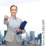 Купить «Привлекательная деловая женщина с папкой и ключами на фоне города», фото № 5683097, снято 19 января 2014 г. (c) Syda Productions / Фотобанк Лори