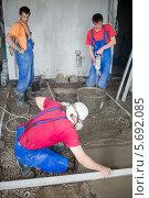 Купить «Трое рабочих в комнате готовят смесь для заливки пола», фото № 5692085, снято 3 июля 2013 г. (c) Losevsky Pavel / Фотобанк Лори