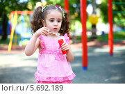 Купить «Маленькая девочка с хвостиками стоит с банкой мыльных пузырей на детской площадке», фото № 5692189, снято 4 июня 2013 г. (c) Losevsky Pavel / Фотобанк Лори