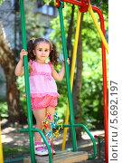 Купить «Счастливая маленькая девочка с хвостиками стоя качается на качелях на детской площадке», фото № 5692197, снято 4 июня 2013 г. (c) Losevsky Pavel / Фотобанк Лори