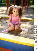 Купить «Маленькая кудрявая девочка сидит в песочнице в летний день», фото № 5692213, снято 4 июня 2013 г. (c) Losevsky Pavel / Фотобанк Лори