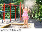Купить «Маленькая девочка стоит в песочнице и бросает вверх песок на детской площадке», фото № 5692221, снято 4 июня 2013 г. (c) Losevsky Pavel / Фотобанк Лори