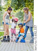 Купить «Две девушки учат двоих детей кататься на роликах», фото № 5692337, снято 4 июля 2013 г. (c) Losevsky Pavel / Фотобанк Лори