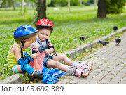 Купить «Двое детей на роликах сидят в парке и кормят птиц», фото № 5692389, снято 4 июля 2013 г. (c) Losevsky Pavel / Фотобанк Лори