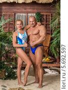 Купить «Мускулистый мужчина и девушка в купальнике стоят на песке у деревянного дома», фото № 5692597, снято 3 октября 2013 г. (c) Losevsky Pavel / Фотобанк Лори