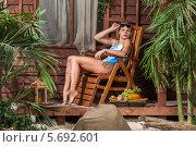 Купить «Красивая девушка в купальнике загорает на деревянном раскладном шезлонге возле дома», фото № 5692601, снято 3 октября 2013 г. (c) Losevsky Pavel / Фотобанк Лори