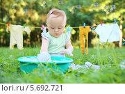 Купить «Маленькая девочка стирает одежду в небольшом зеленом тазике на траве», фото № 5692721, снято 20 июня 2013 г. (c) Losevsky Pavel / Фотобанк Лори
