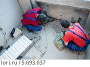 Купить «Двое мужчин в спец одежде  устанавливают крепление для батарее под окном в квартире с черновой отделкой», фото № 5693037, снято 22 июня 2013 г. (c) Losevsky Pavel / Фотобанк Лори