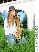 Купить «Девушка  в шляпе играет на саксофоне в парке в солнечный день», фото № 5693453, снято 6 июня 2013 г. (c) Losevsky Pavel / Фотобанк Лори