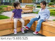 Купить «Темнокожие девочка и мальчик на скамейках в парке», фото № 5693525, снято 30 мая 2013 г. (c) Losevsky Pavel / Фотобанк Лори
